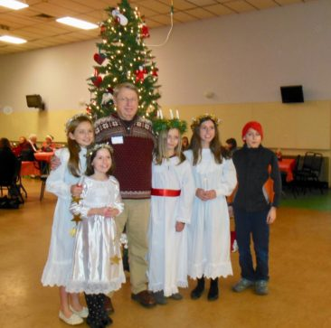 Maine Nordmenn lodge past president Herb Hoppe poses with his granddaughters and the Pepper Kale boy following the St. Lucia pageant at Juletrefest