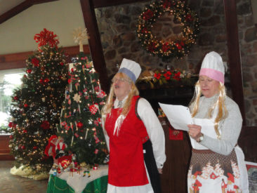"""Gunhild (District VP Kathy Dollymore) and Severine (Sylvia Illuzzi) sing """"Roll Out The Lefse"""" at the 2017 Restauration Lodge Christmas party"""