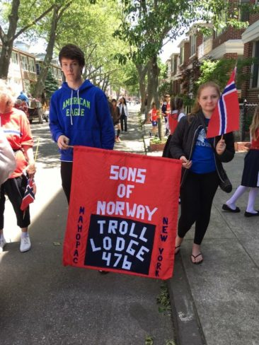 William Dickson and Emily Brideau are proudly carrying the Troll Lodge banner in the Syttende Mai parade